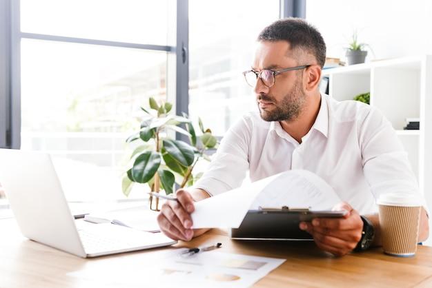 Kluger geschäftsmann 30s im weißen hemd, das informationen von papierdokumenten unter verwendung des laptops während der arbeit im büro überprüft