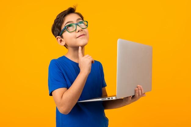 Kluger junge in einem blauen t-shirt, der denkt, einen laptop in seinen händen auf gelb zu halten
