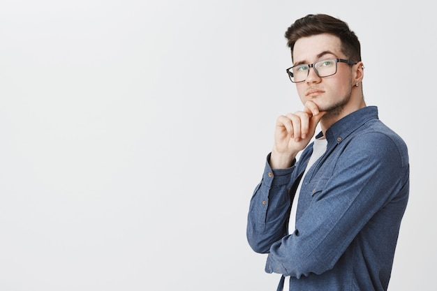 Kluger junger mann in den gläsern, die nachdenkliche, nachdenkliche idee suchen