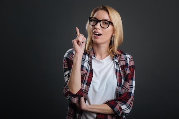 Kluger kopf. motivierte fleißige junge frau, die ihre aufmerksamkeit auf sich zieht, indem sie ihren finger nach oben zeigt und ihre meinung äußert
