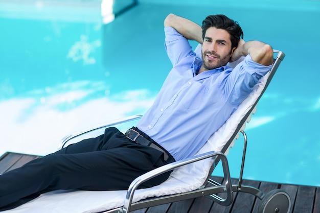 Kluger mann, der auf sunlounger sich entspannt