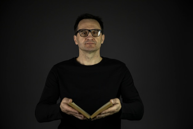 Kluger mann in freizeitkleidung und brille hält altes offenes buch und schaut in die kamera