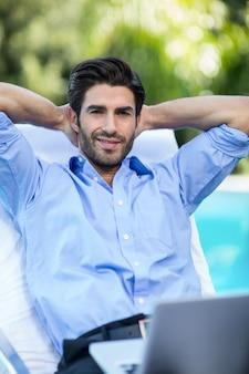 Kluger mann mit einem laptop, der auf sonnenruhesessel sich entspannt