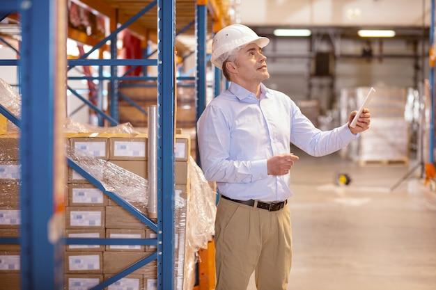 Kluger qualifizierter mann, der eine tablette hält, während er als manager im lager arbeitet