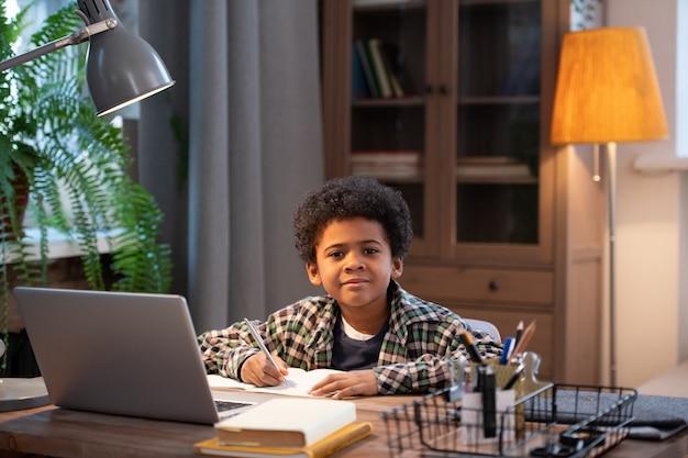 Kluger und fleißiger afrikanischer schuljunge, der notizen im heft macht und dich ansieht, während er am tisch vor dem laptop im wohnzimmer sitzt