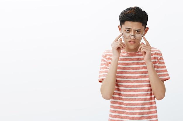 Kluger und fokussierter hübscher junger männlicher asiatischer student, der versucht, ein hartes rätsel zu lösen, brille abzunehmen, die stirn runzelt, während er daran denkt, tempel zu berühren, die versuchen, eine antwort zu finden