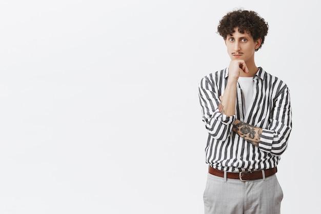 Kluger und nachdenklicher junger kreativer männlicher unternehmer mit tätowiertem armschnurrbart und lockigem haar im trendigen formellen gestreiften hemd und in der hose, die sich auf faust stützen und ernsthaft schauen