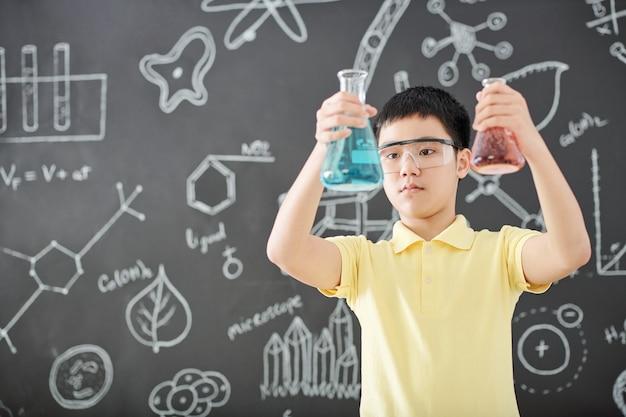 Kluger vietnamesischer schüler in der schutzbrille, die becher mit bunten flüssigkeiten in seinen händen betrachtet, tafel mit zeichnungen