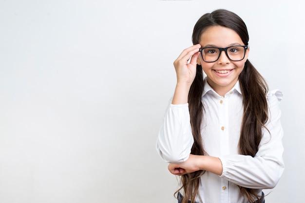 Kluges hispanisches schulmädchen, das in den gläsern steht