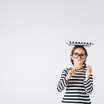 Kluges Mädchen mit Notizbüchern auf Kopf