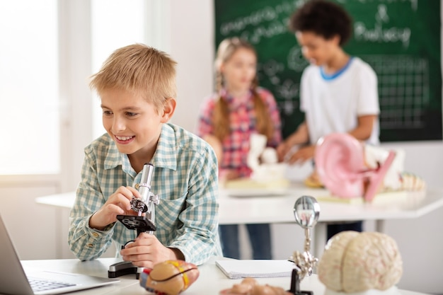 Kluges schulkind. positiv entzückter junge, der den laptopbildschirm beim lernen in der schule betrachtet