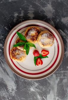 Klumpenpfannkuchen mit erdbeerminze und puderzucker in einer weißen platte.