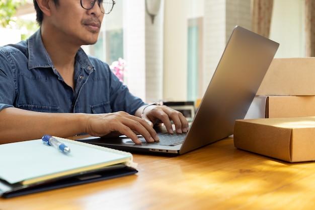 Kmu-geschäftsmann, der auf dem tisch an laptop mit paketkasten arbeitet
