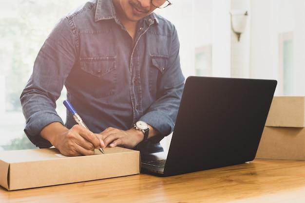 Kmu-geschäftsmann-schreibensadresse auf paket mit labtop auf dem tisch.