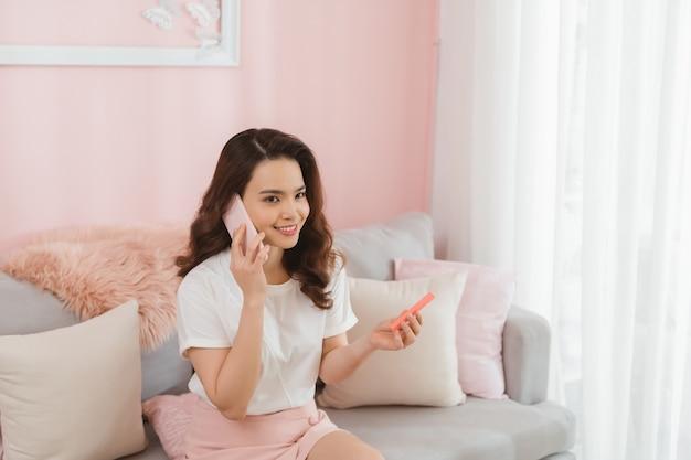 Kmu junge frau, die eigentümerin am online-shopping-shop arbeitet und bestellung vom kunden auf mobiltelefon entgegennimmt.