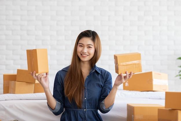 Kmu-unternehmerin von jungen asiatischen frauen, die mit laptop für online-einkäufe zu hause arbeiten, fröhlich und glücklich mit box für verpackung zu hause