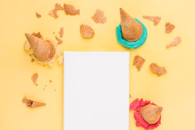 Knackige waffeln mit heller eiscreme und leeres blatt papier abschöpfen