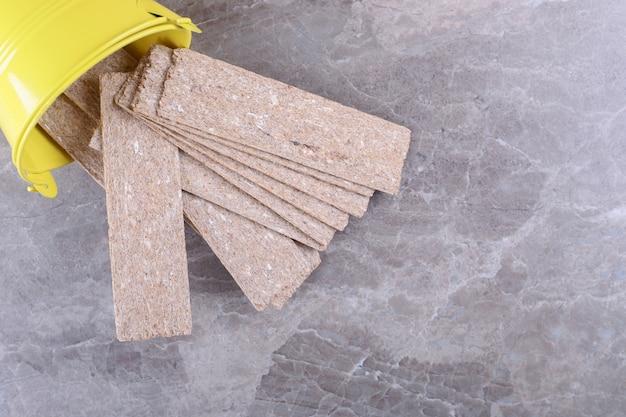 Knäckebrot fällt aus dem umgestürzten gelben eimer auf die marmoroberfläche