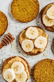 Knäckebrot mit erdnussbutter, banane und honig, draufsicht. veganes lebensmittelkonzept.