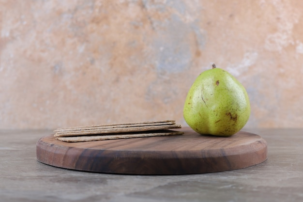 Knäckebrot und birne auf dem brett, auf der marmoroberfläche