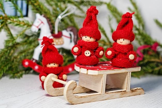 Knallrote spielzeugkinder in gestrickter kleidung auf dem schlitten des weihnachtsmanns mit weihnachtsbaum und einem spielzeugpferd.