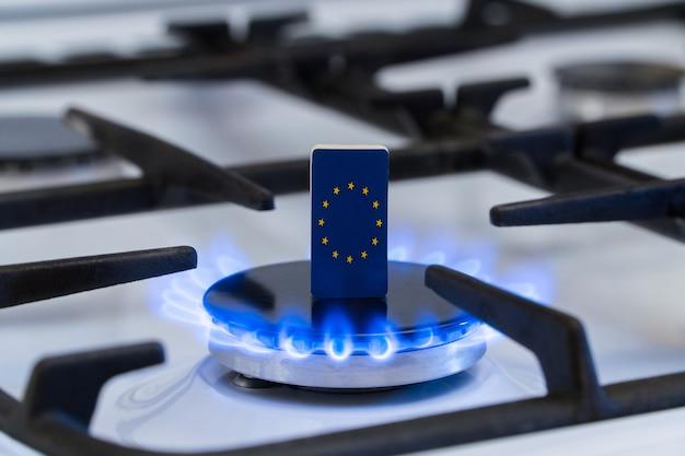 Knappheit und gaskrise. flagge der europäischen union auf einem brennenden gasherd