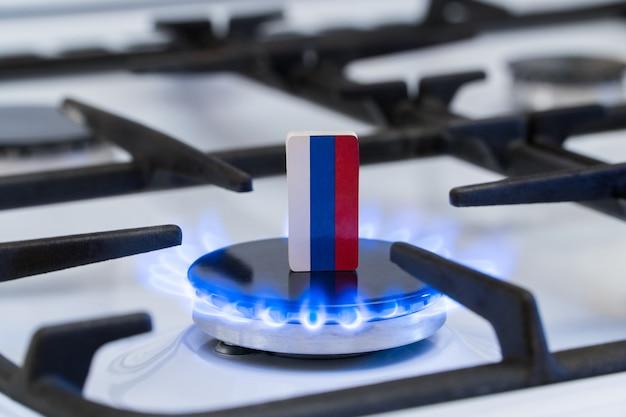 Knappheit und gaskrise. flagge der russen auf einem brennenden gasherd