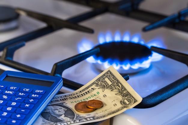 Knappheit und gaskrise. geld und ein taschenrechner auf dem hintergrund eines brennenden gasherdes