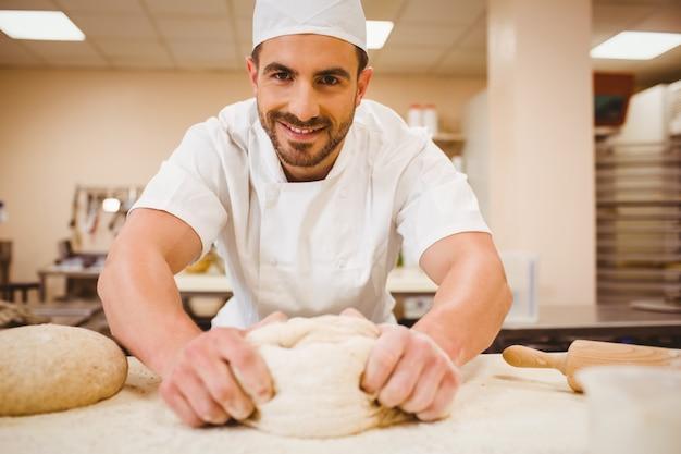 Knetender teig des bäckers an einem zähler in einer handelsküche