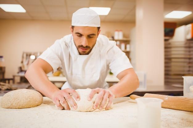 Knetender teig des bäckers an einer theke