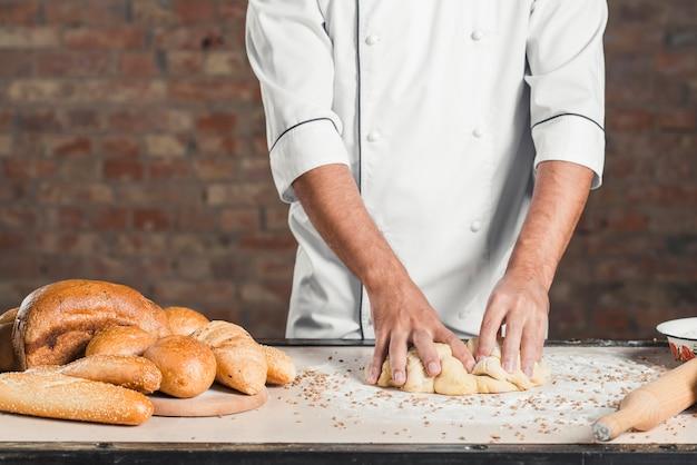 Knetender teig des männlichen bäckers auf küche worktop mit vielen gebackenen broten