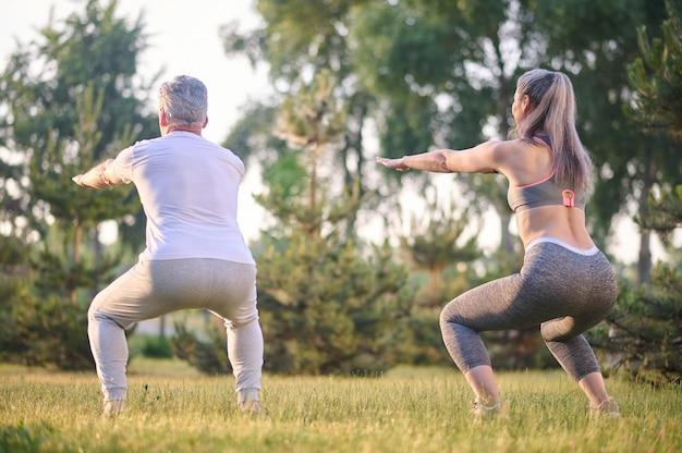 Kniebeugen. ein mann und eine frau hocken während des trainings im park