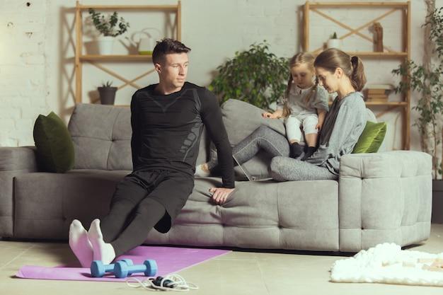 Kniebeugen. junger mann, der zu hause fitness, aerobic, yoga, sportlichen lebensstil und heimgym ausübt. aktiv werden während des lockdowns, quarantäne. gesundheitswesen, bewegung, wellness-konzept.