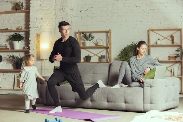 Kniebeugen. junger mann, der zu hause fitness, aerobic, yoga, sportlichen lebensstil und heimgym ausübt.