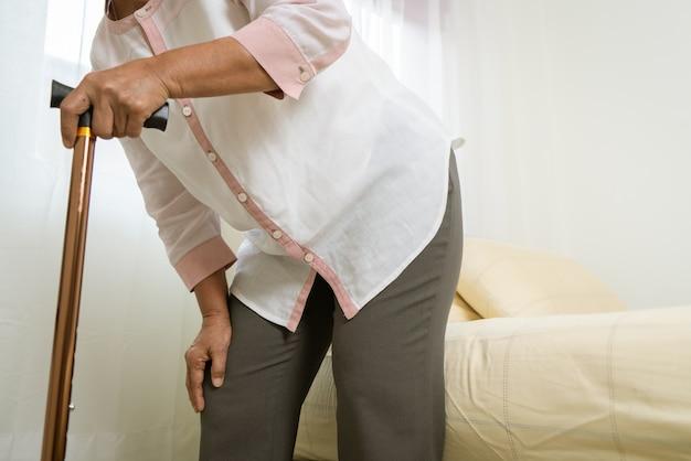 Knieschmerzen der älteren frau mit stock, gesundheitsproblem des älteren konzepts