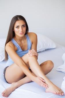 Knieschmerzen. unglückliche frau, die zu hause unter den schmerz im bein leidet