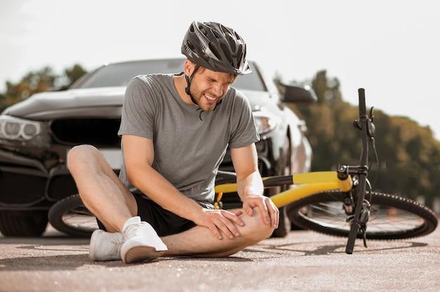 Knieverletzung. junger erwachsener verletzter radfahrer im helm, der das knie auf der straße in der nähe des umgefallenen fahrrads vor dem auto hält