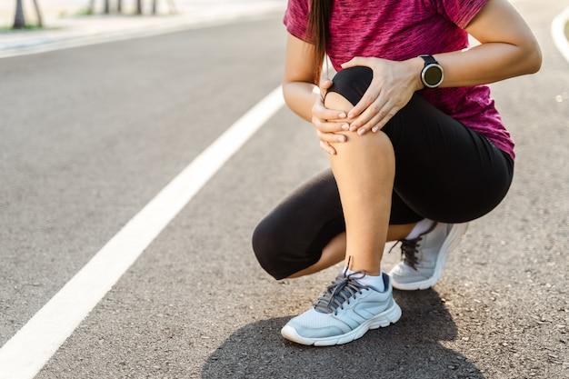 Knieverletzungen. sportfrau mit starken athletischen beinen, die knie mit ihren händen im schmerz halten, nachdem sie muskelverletzung während eines lauftrainingstrainings auf der laufbahn erlitten haben. gesundheits- und sportkonzept.