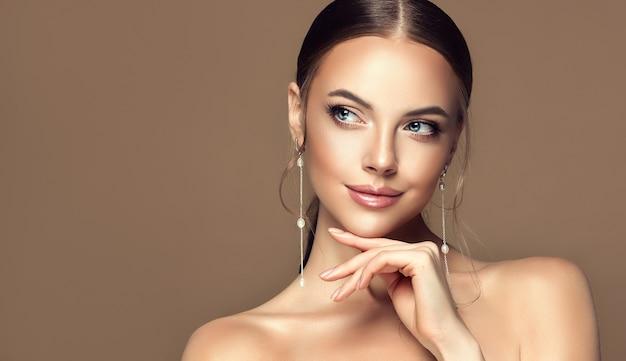 Kniffliger blick beiseite und elegantes gestenporträt von make-up und stil der jungen schönen frau
