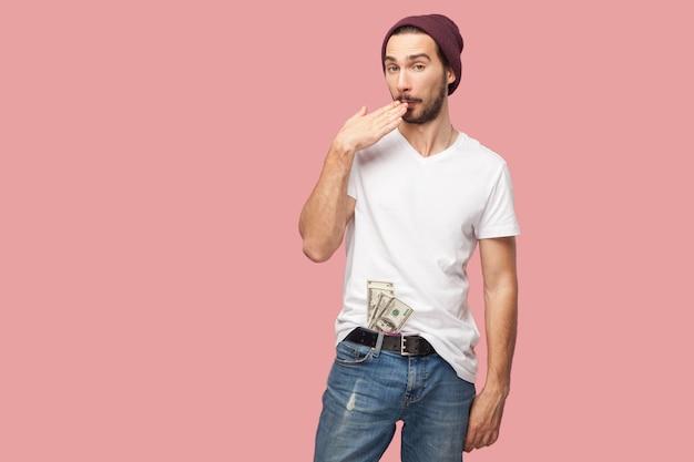 Kniffliger, gutaussehender, bärtiger junger hipster-mann in weißem hemd und lässigem hut, der viele dollar-geld auf der tasche hält, mit unglaublichem gesicht. innen, isoliert, studioaufnahme, rosa hintergrund