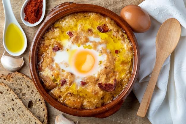 Knoblauch-brot-suppe (kastilisch, aus spanien) im tontopf und seinen hauptzutaten.