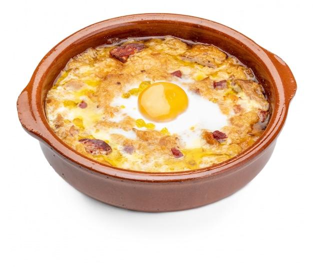 Knoblauch-brot-suppe (spanisch, aus spanien) im tontopf. sicht von oben. isoliert.