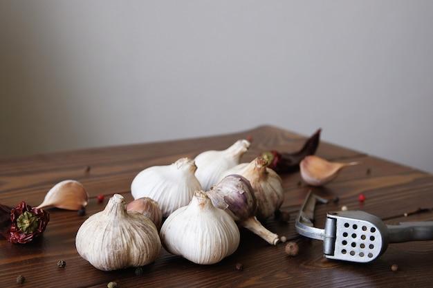 Knoblauch, knoblauchzehen und gewürze auf einem holztisch. exquisite gewürze. natürlicher geschmack. antibakteriell, stärkt die immunität. das konzept der gesunden bio-lebensmittel, alternativmedizin