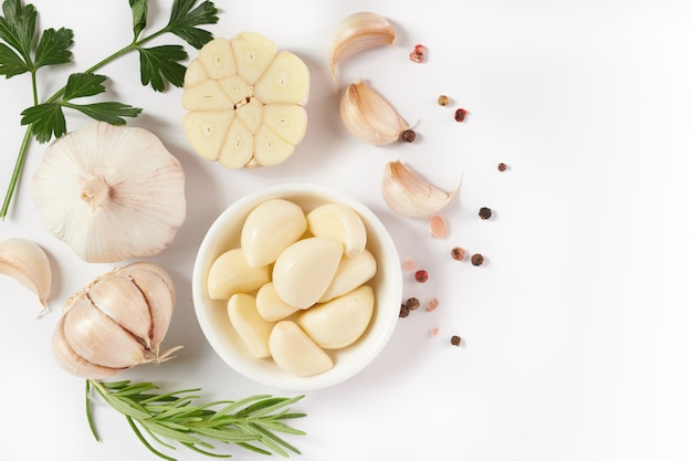 Knoblauch mit rosmarin, petersilie und pfefferkorn isoliert auf weißer oberfläche. draufsicht. flach liegen. frisch gepflückt aus heimischem bio-garten. lebensmittelkonzept.
