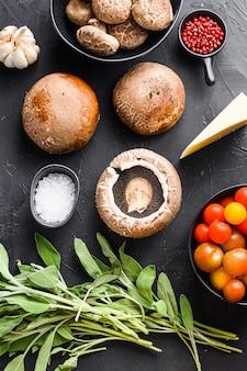Knoblauch-portabello-pilze-zutaten zum backen, cheddar-käse und salbei auf schwarzem hintergrund. ansicht von oben.