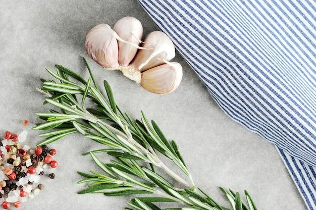Knoblauch, rosmarin und gewürze mit einer gestreiften tischdecke