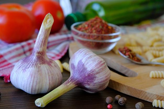 Knoblauch, rote tomaten, trockene georgische gewürze für feinschmecker, olivenöl, teigwaren auf einem holztisch.