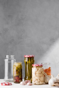 Knoblauch, spargel und oliven in gläsern mit kopierraum aufbewahrt