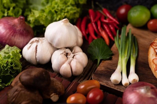 Knoblauch, tomate, shiitake-pilz, chili und rote zwiebel auf holzlatten