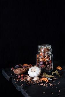 Knoblauch, trockenfrüchte und samen in dunkler rustikaler oberfläche. künstlerisches foto des knoblauchs und der trockenen frucht in einem glas auf alter schwarzer tabelle schoss in zurückhaltender ciaroscurro art